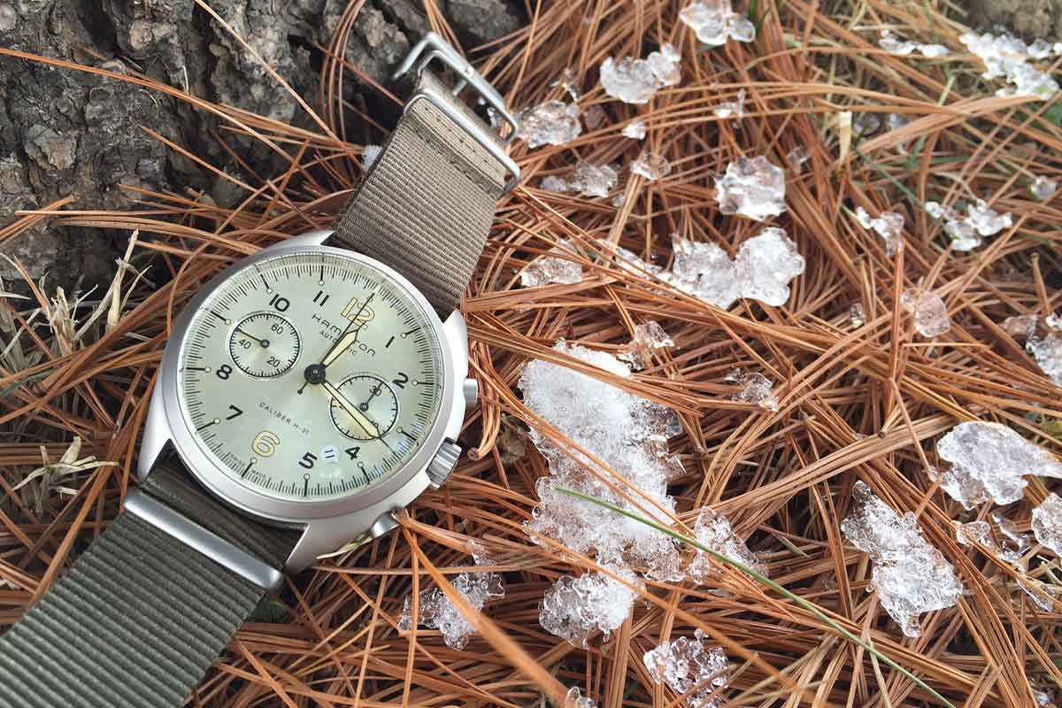 Hamilton Khaki Pioneer Pilot by the trunk of a white pine tree in the snow.
