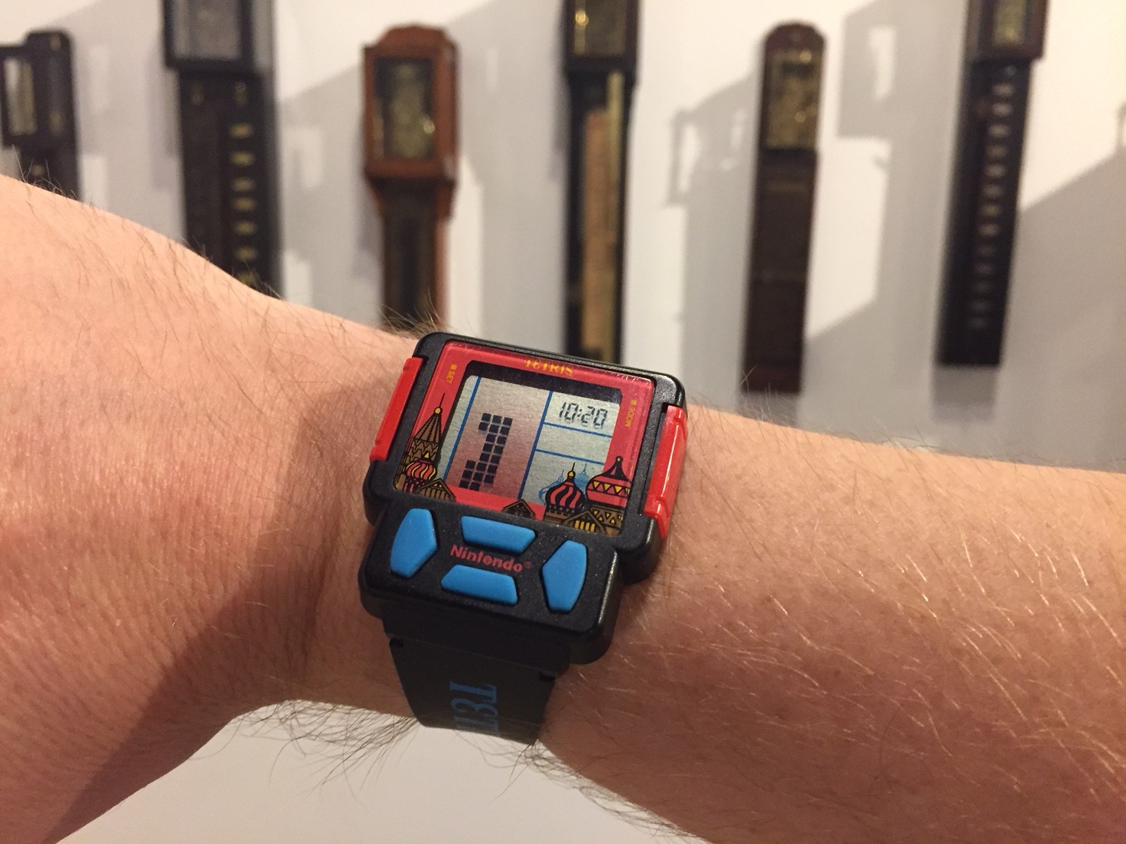 Tetris watch on man's wrist with Japanese shaku-dokei clock display in background at the National Watch & Clock Museum