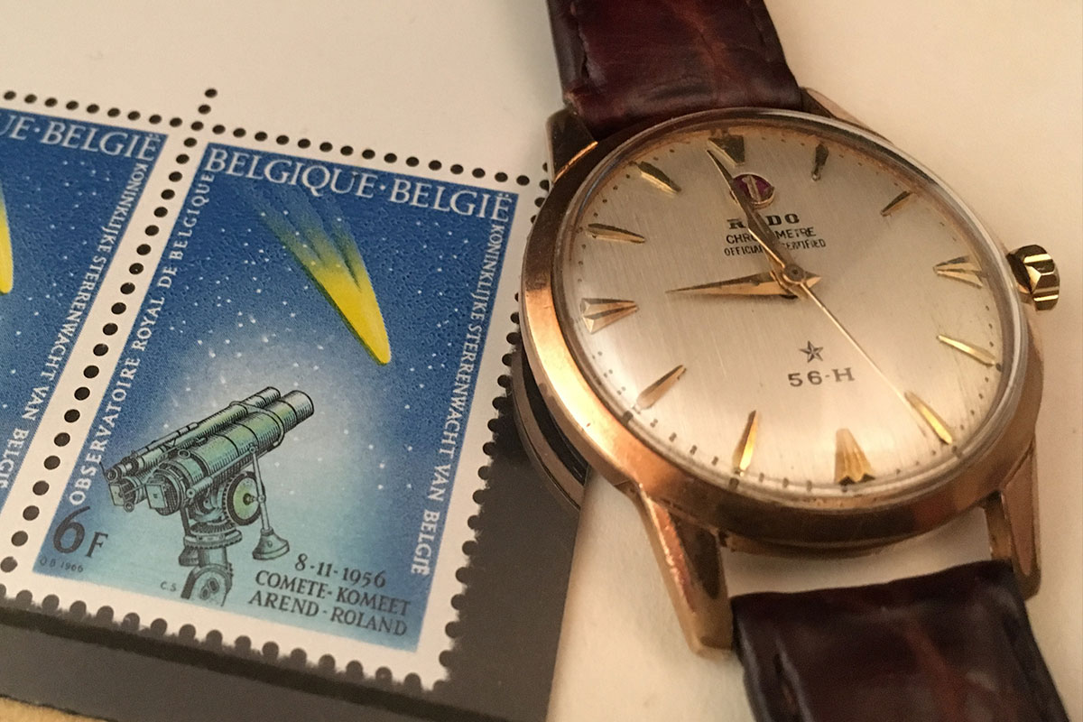 Vintage Rado wristwatch beside a postage stamp depicting a telescope viewing a comet in a night sky